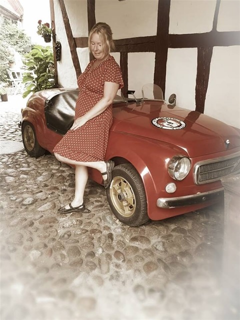 Anki lutandes mot en röd bil