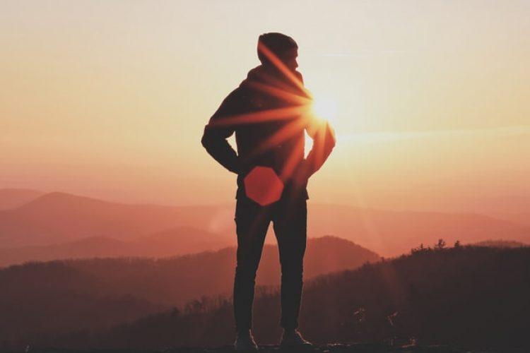 Kille som står på ett berg